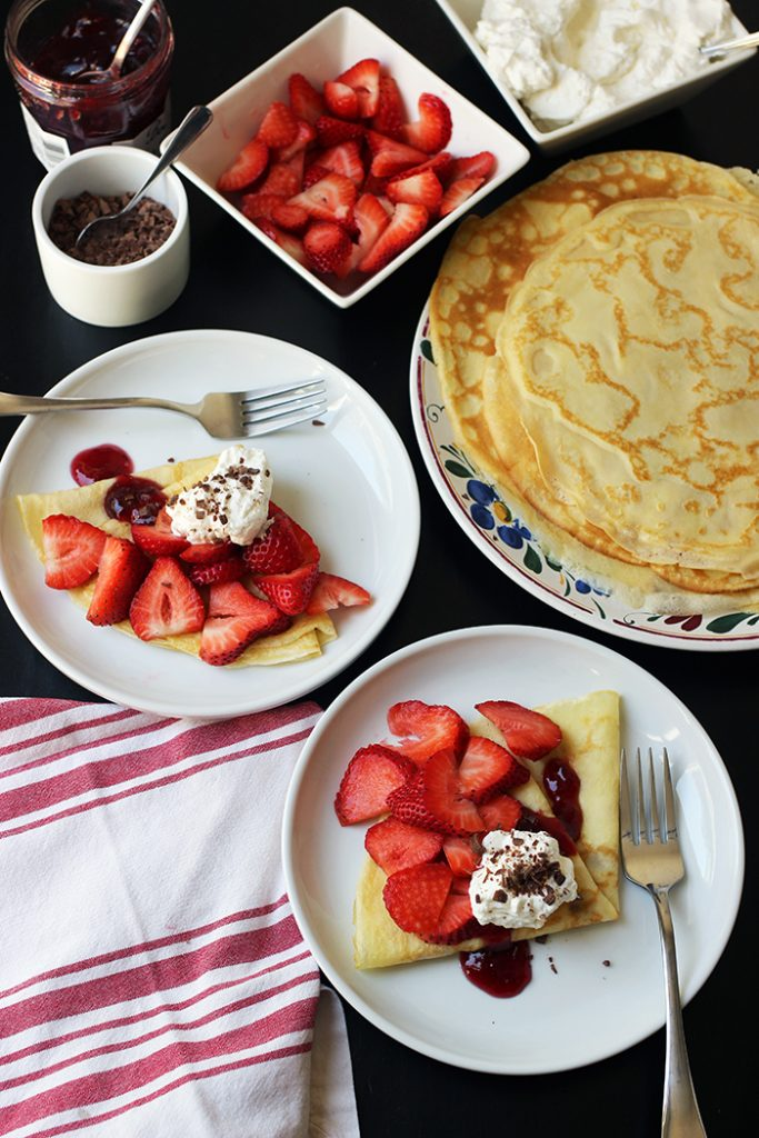 two plates of dessert crepes with toppings