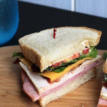 Club Sandwich cut in half on wooden board