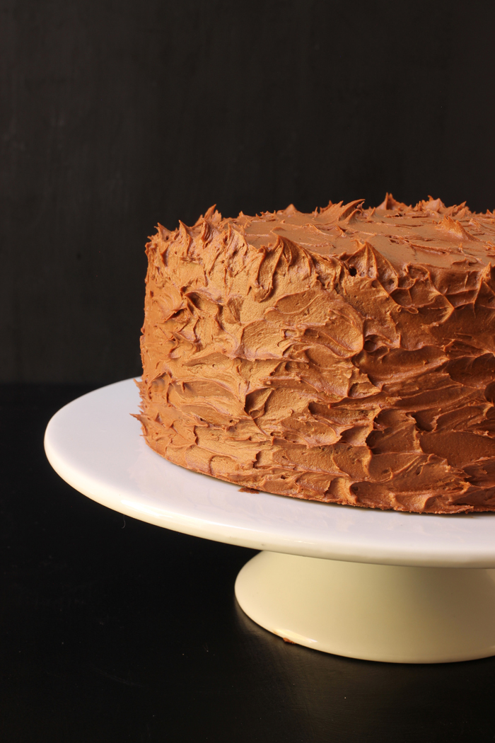 cake on pedastal with chocolate buttercream