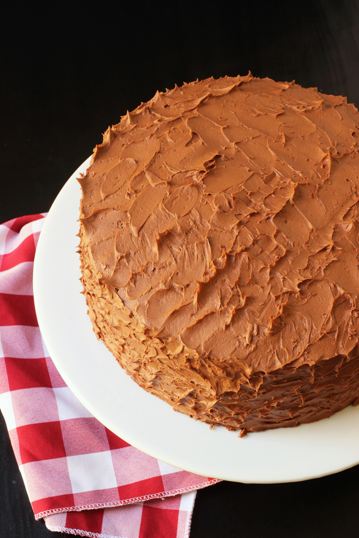 chocolate cake on white pedastal with red checked cloth