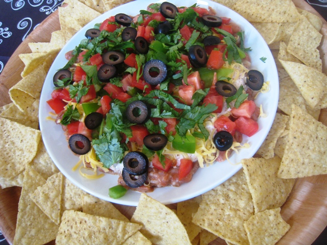 A plate of chips and platter of seven layer dip