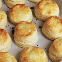 Flaky Buttermilk Biscuits cooling on parchment-lined tray