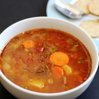 A bowl of soup with crackers