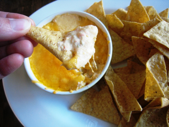 dipping a chip into cheese dip