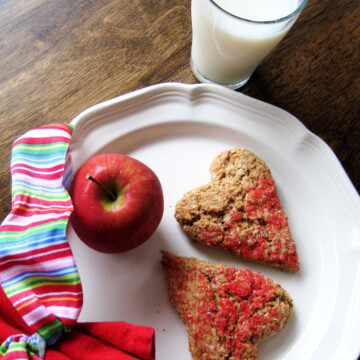 heart shaped scones on a white plate with a glass of milk