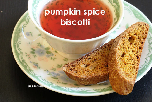 two Pumpkin Spice Biscotti cookies on a plate with a cup of tea
