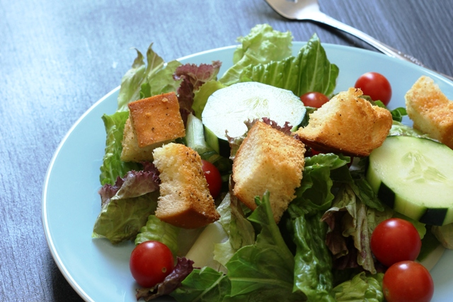 A plate of salad with croutons