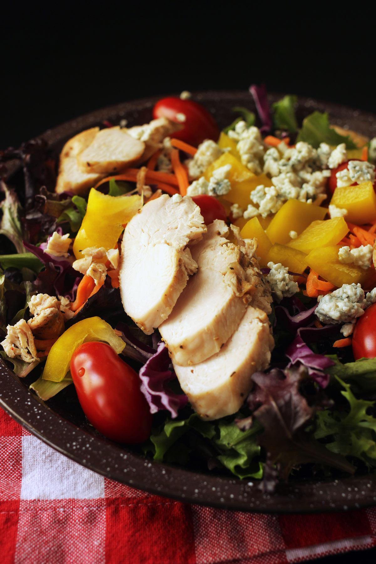 grilled chicken strips atop salad