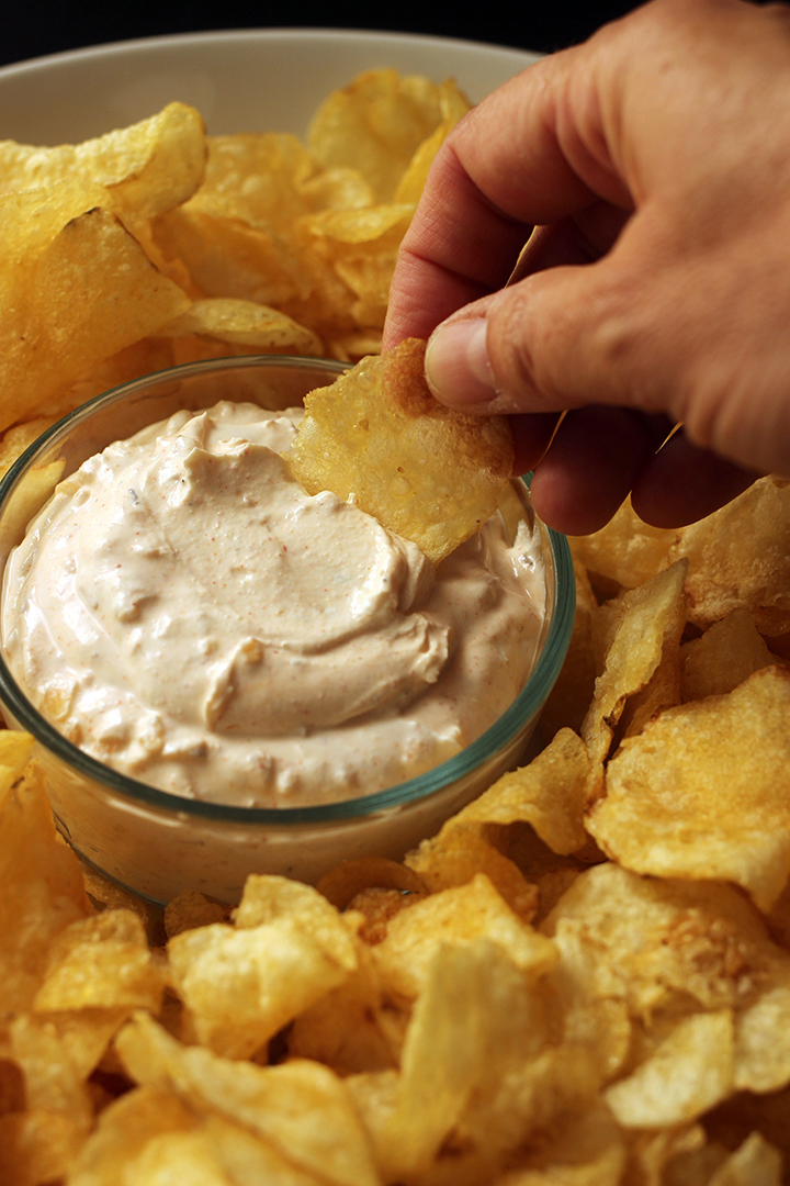 hand dipping potato chip into onion dip