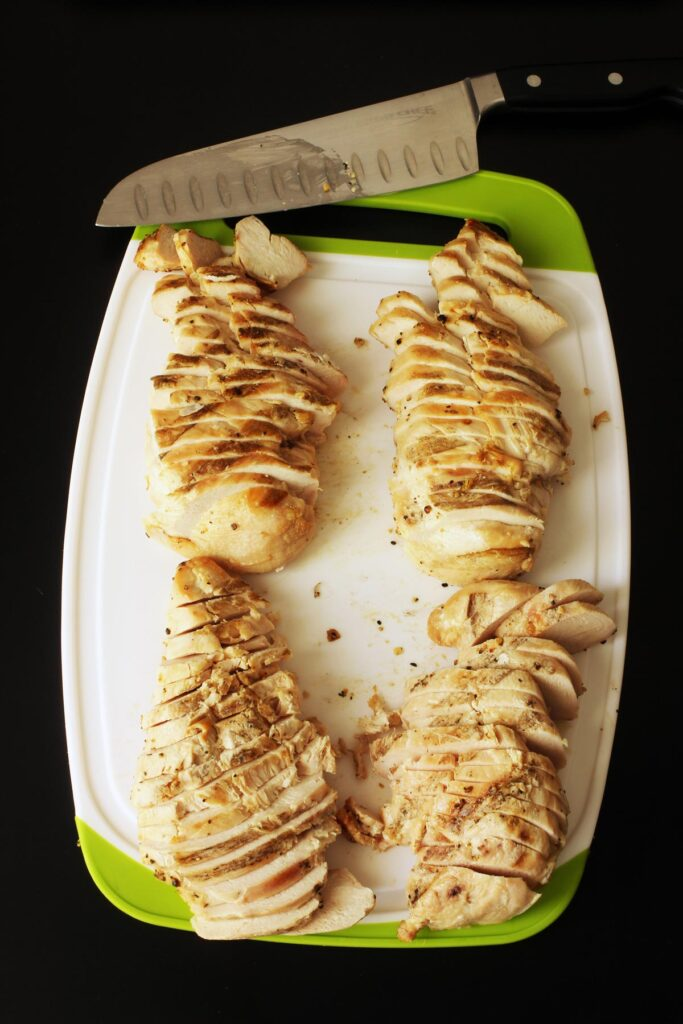 sliced chicken breasts on cutting board