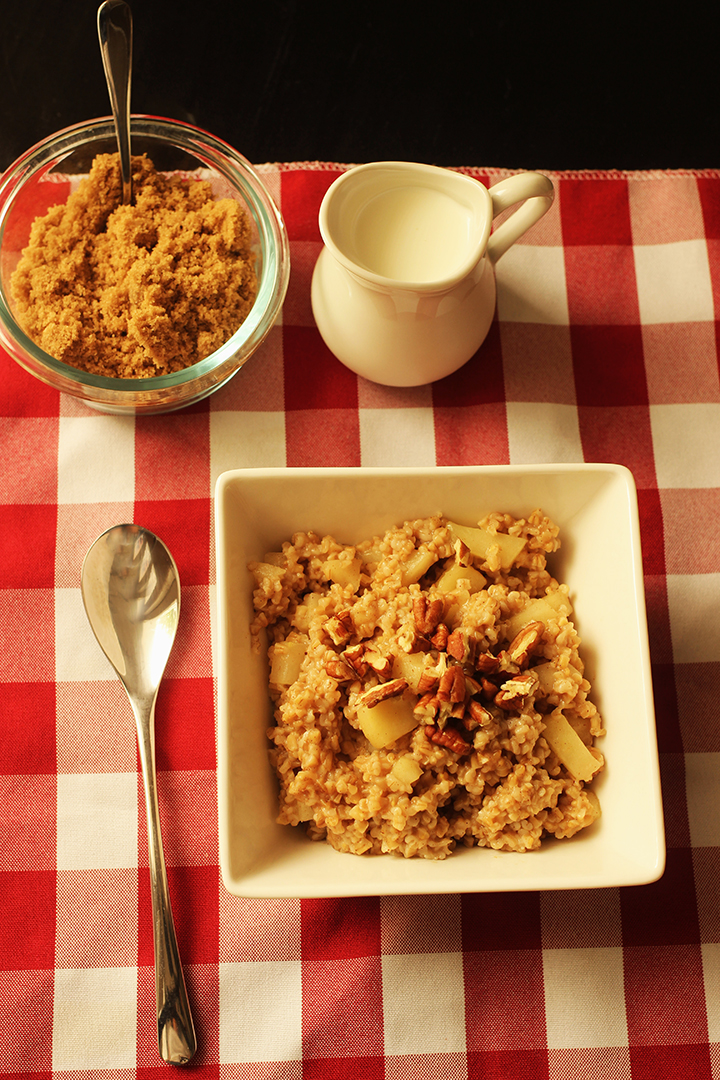 table set with bowl of brown sugar, pitcher of cream and bowl of oatmeal