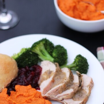 A plate of Thanksgiving food on a table, with bowls