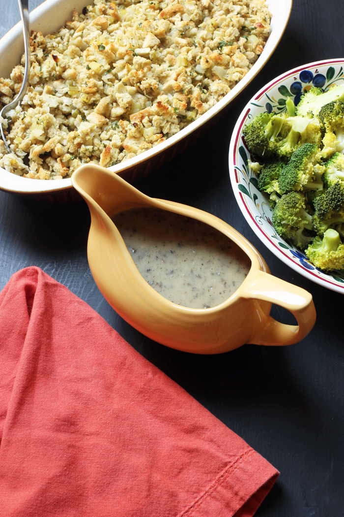 gravy boat next to bowls of broccoli and stuffing