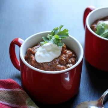 mugs of chili with sour cream and cilantro