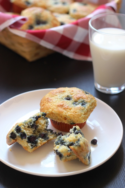 A close up of a plate of muffins and glass of milk