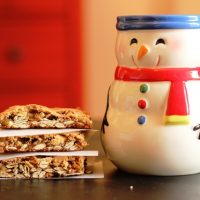 stack of cookie bars next to snowman mug