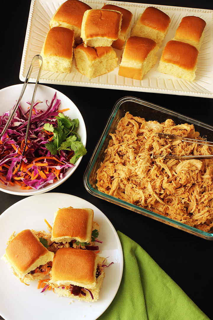 dinner table set with sweet and sour pulled chicken rolls and cabbage with a dinner plate