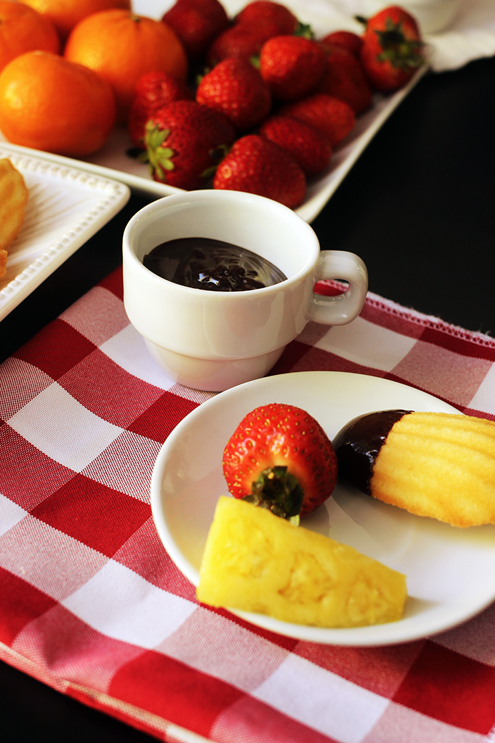 espresso cup with fondue next to plates of fruit