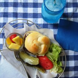 a basket of hamburger and toppings