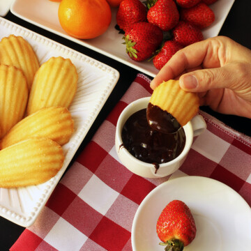 hand dipping madeleine into chocolate fondue next to plates of dippers