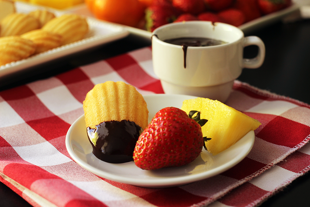 madeleine dipped in chocolate on plate with strawberry with pineapple