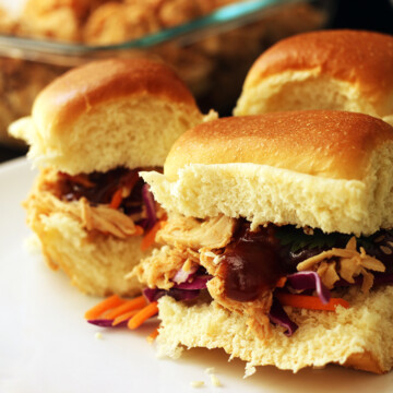 plate of sandwiches next to dish of pulled chicken