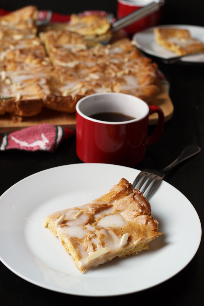 slice of kringle on plate with cup of coffee