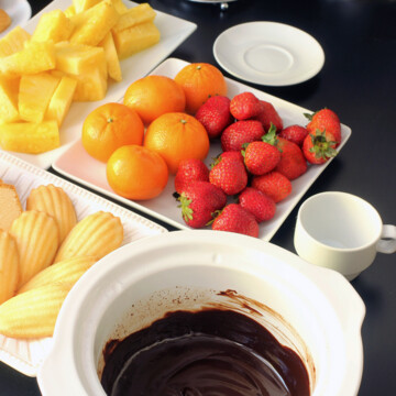 slow cooker crock full of chocolate fondue with plates of fruit and cake