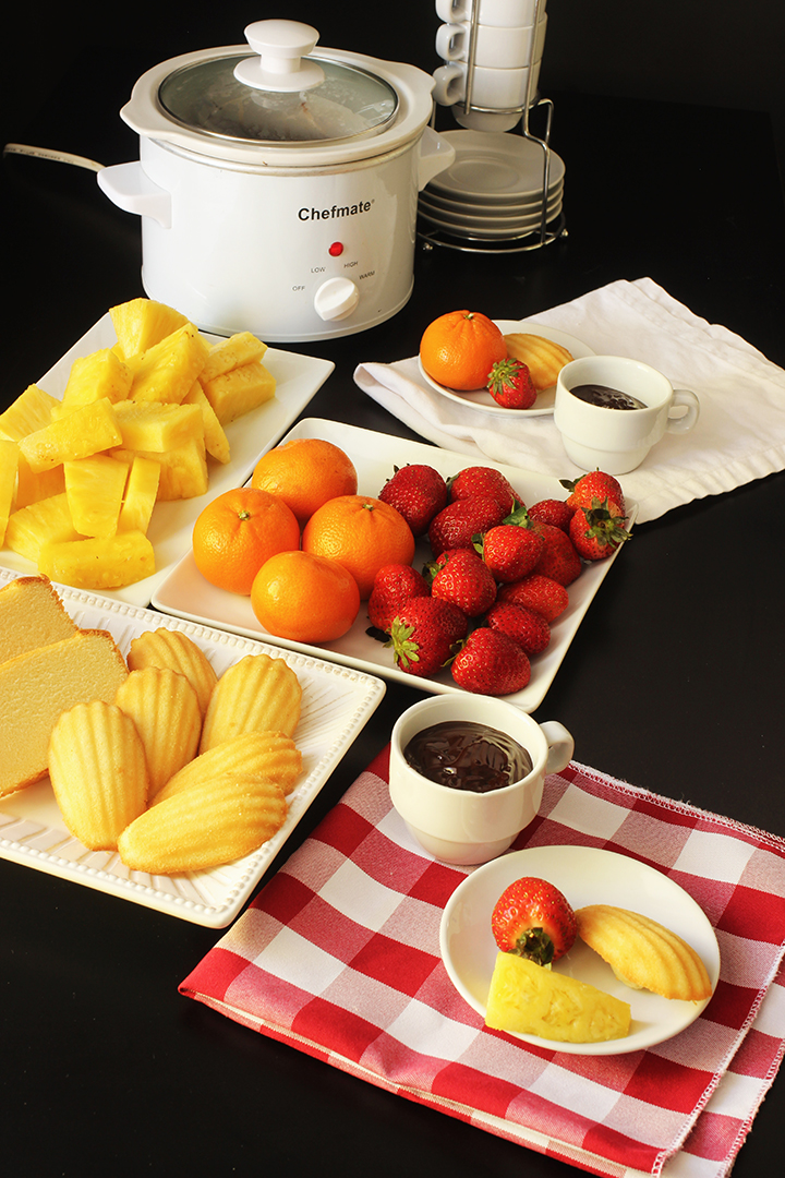 slow cooker of chocolate fondue on table with plates of cake and fruit