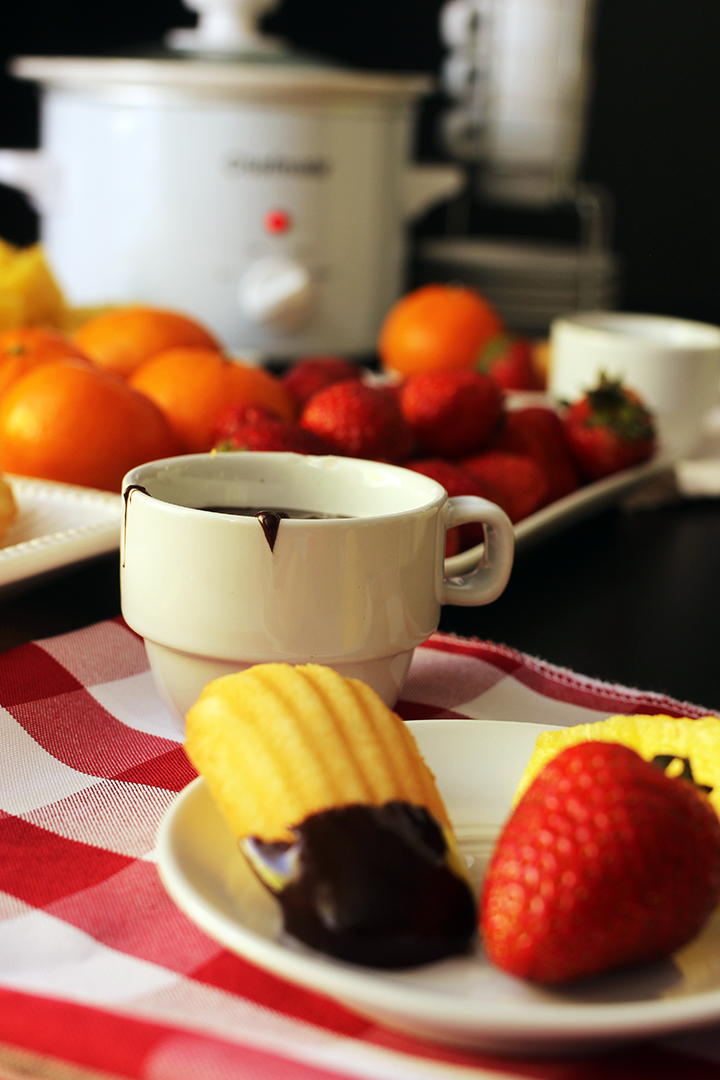 slow cooker on table with fruit and cup of chocolate fondue