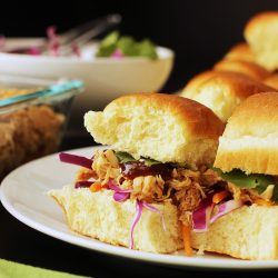 sweet and sour pulled chicken on hawaiian rolls on plate
