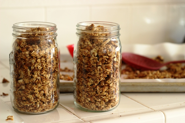 two mason jars on a counter filled with healthy homemade granola.