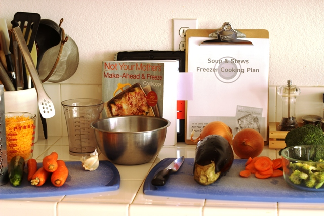 mise en place of vegetables and cutting boards with freezer cookbook