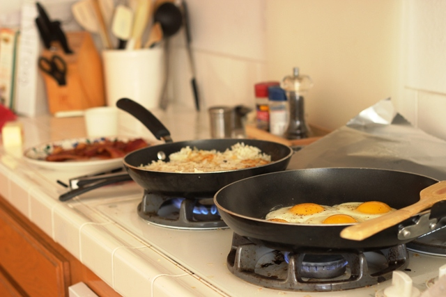 skillets of breakfast cooking on stove