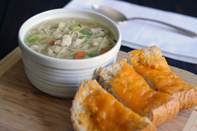 A plate of cheese bread on a table, with Soup