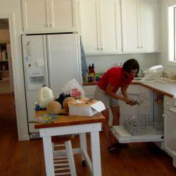 A woman reaching into dishwasher