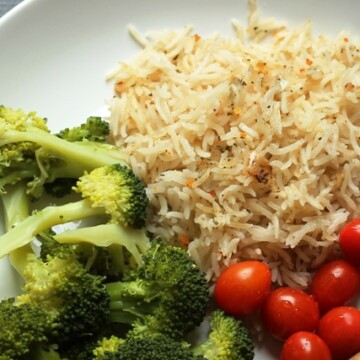 A plate rice and broccoli, with tomatoes
