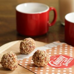 fruit and nut energy bites on board with mugs of milk