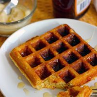 A plate of buttermilk waffle with honey