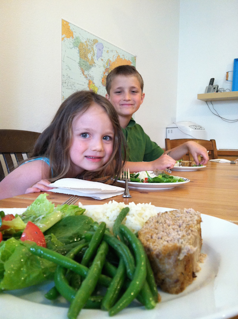 A boy and a little girl sitting at a table with a plate of Meatloaf