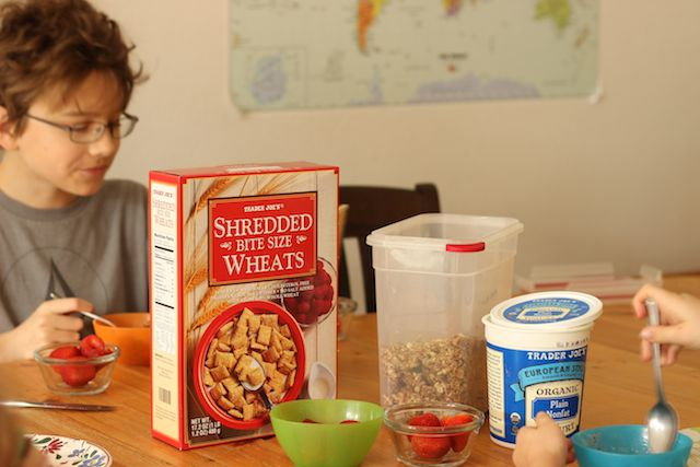 A person sitting at a breakfast table with yogurt and cereal