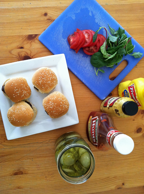 Food on a wooden cutting board, with plate of sliders