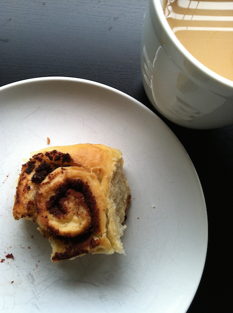 cinnamon roll on plate with cup of coffee
