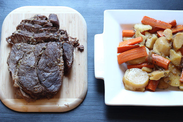 A pot roast on a cutting board with vegetables