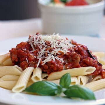 A plate of penne with bolognese on a table