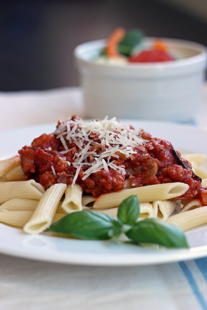 a plate of pasta and meat sauce on top