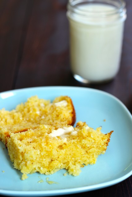 slice of honey cornbread on a plate with a glass of milk