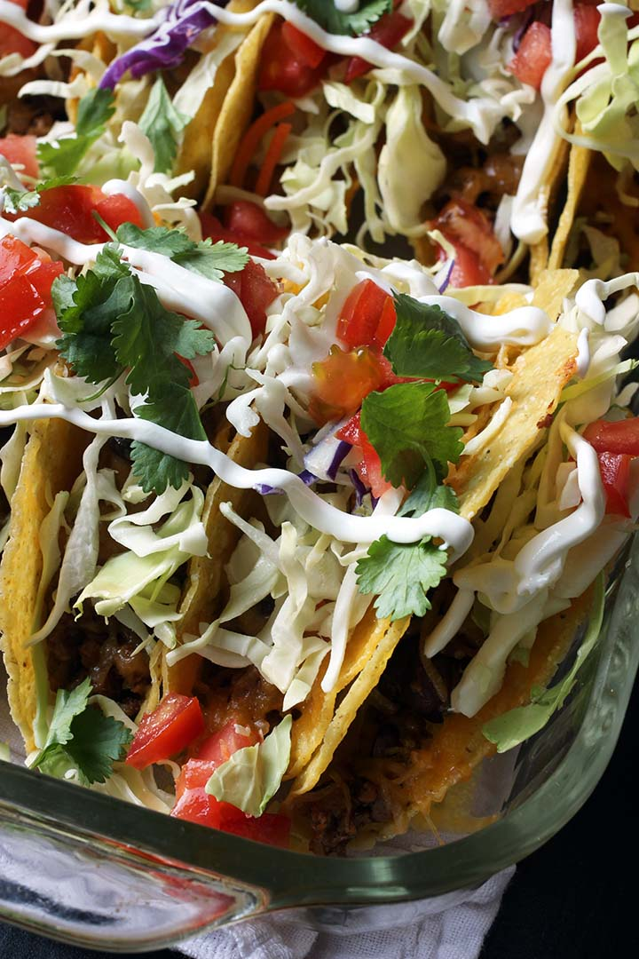 close up of tacos in pyrex pan with toppings