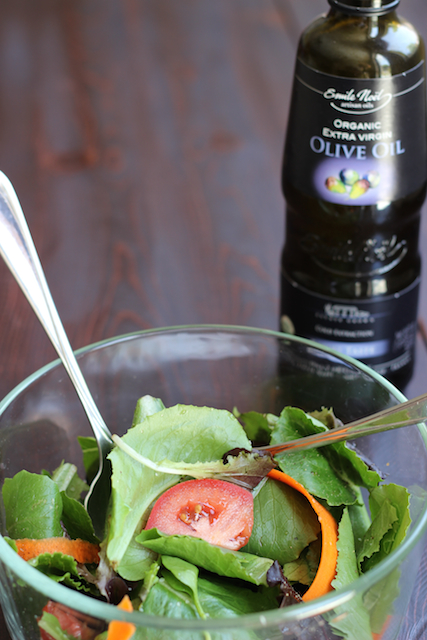 A close up of a bottle of oil next to a bowl of salad