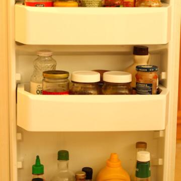 An open refrigerator with full condiment door